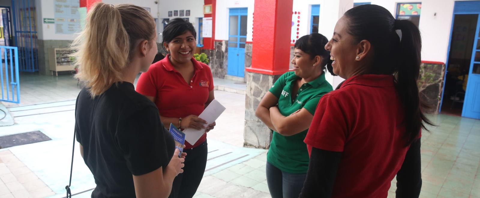 A volunteer talking to local teachers at a school to practice her Spanish with the help of her project expert